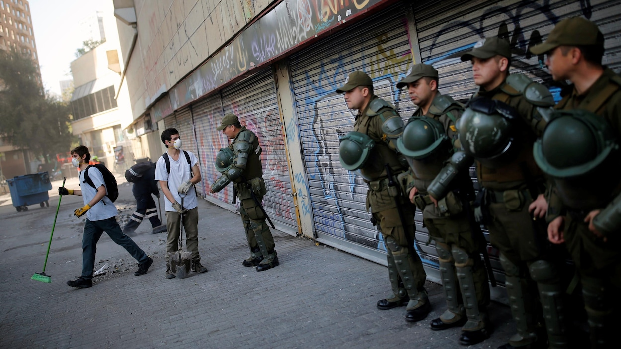 Des agents de police se tiennent devant des portes coulissantes en métal couvertes de graffitis. Un policier parle à un jeune homme qui balaie la rue.