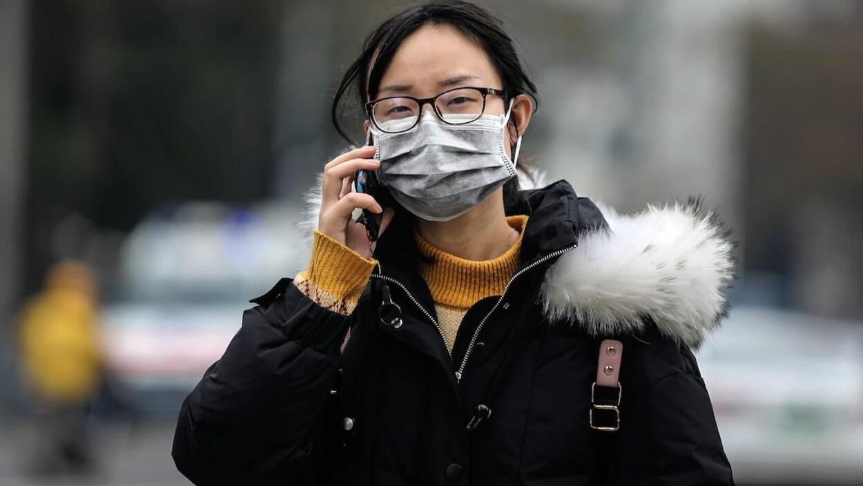 Une femme porte un masque.