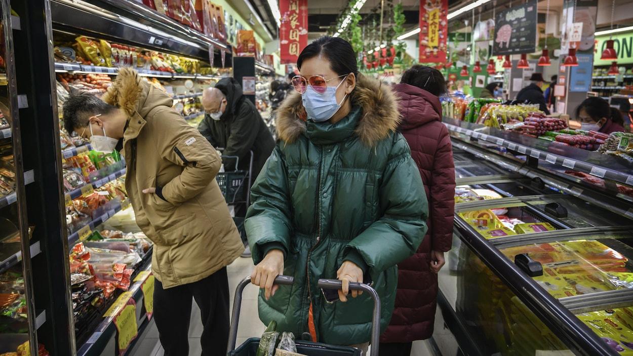 Trois Chinois portent des masques dans une allée d'épicerie.
