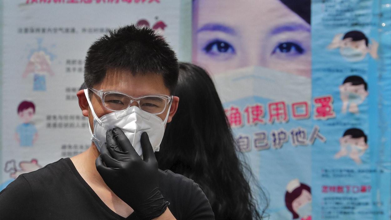 Un homme porte un masque de protection avec en arrière-plan des affiches expliquant la bonne façon de porter un masque facial pour aider à freiner la propagation du coronavirus à Pékin.