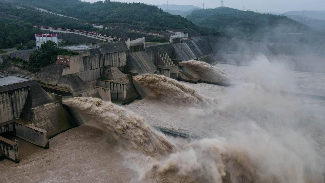Des torrents d'eau boueuse sortent de trois vannes ouvertes.