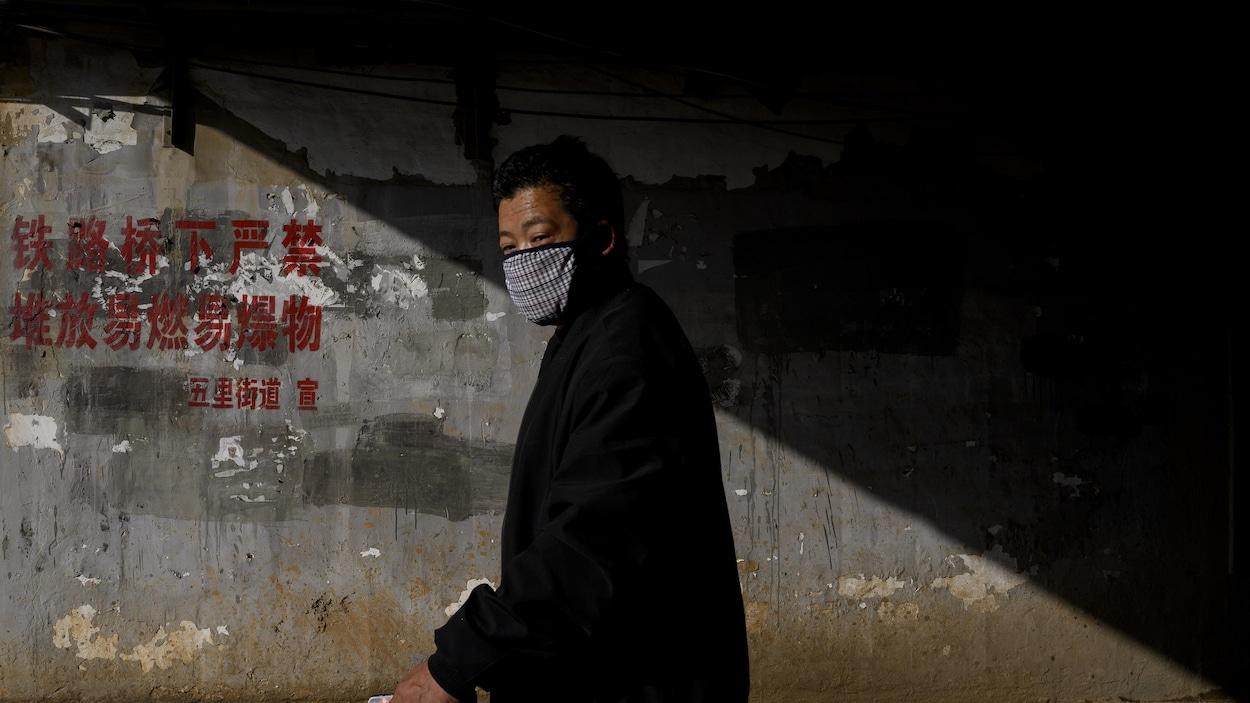 Un homme portant un masque sur la bouche marche dans la pénombre.