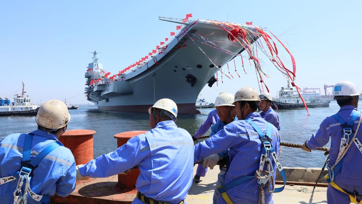 Des ouvriers chinois regardant le porte-avions Shandong.