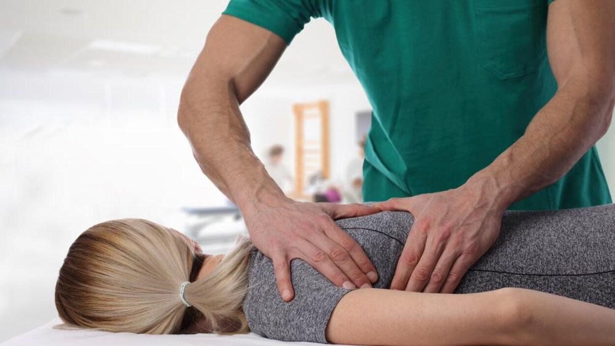 Les mains d'un homme sur le dos d'une femme allongée sur le ventre.