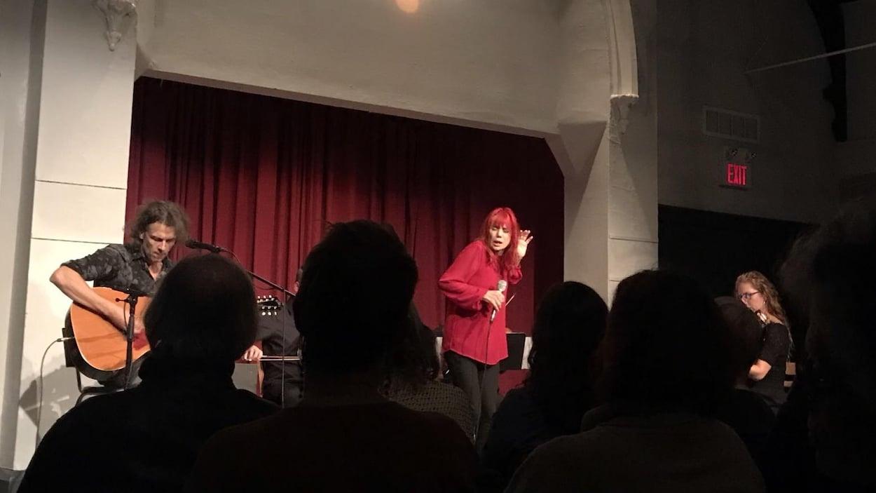 Une femme chante sur scène devant un public aux côtés de musiciens.