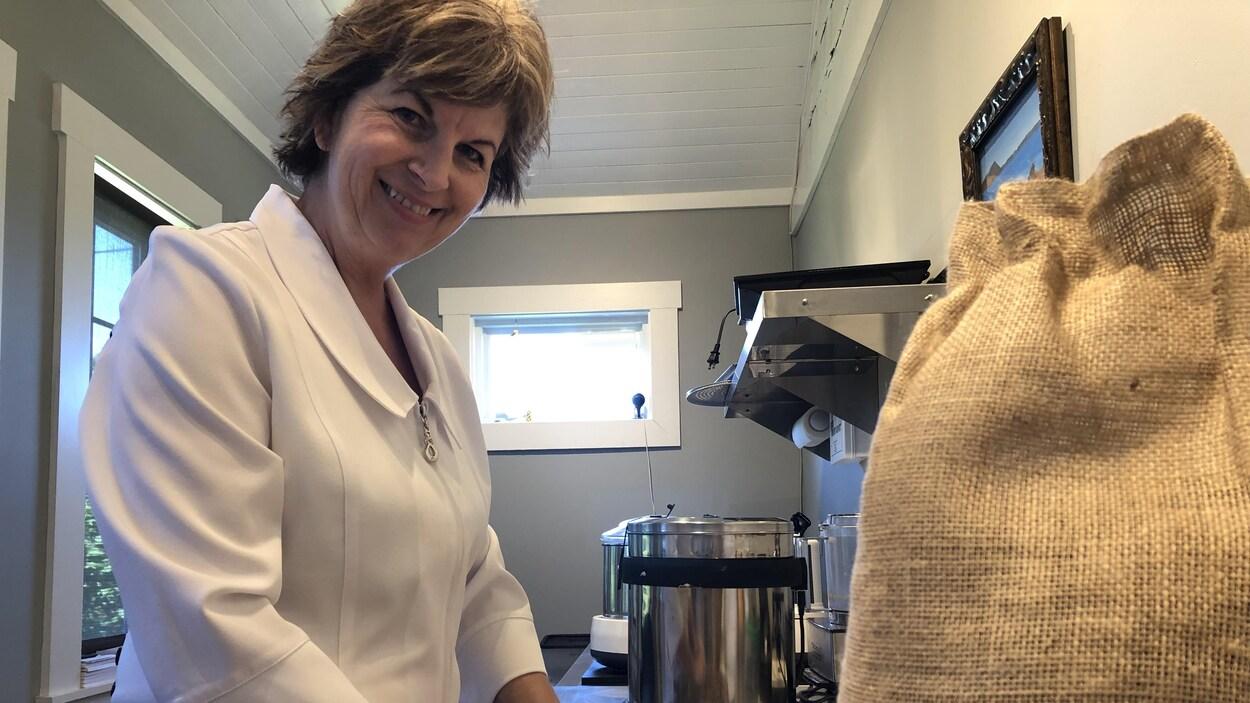 Une femme manipule des fèves de cacao.
