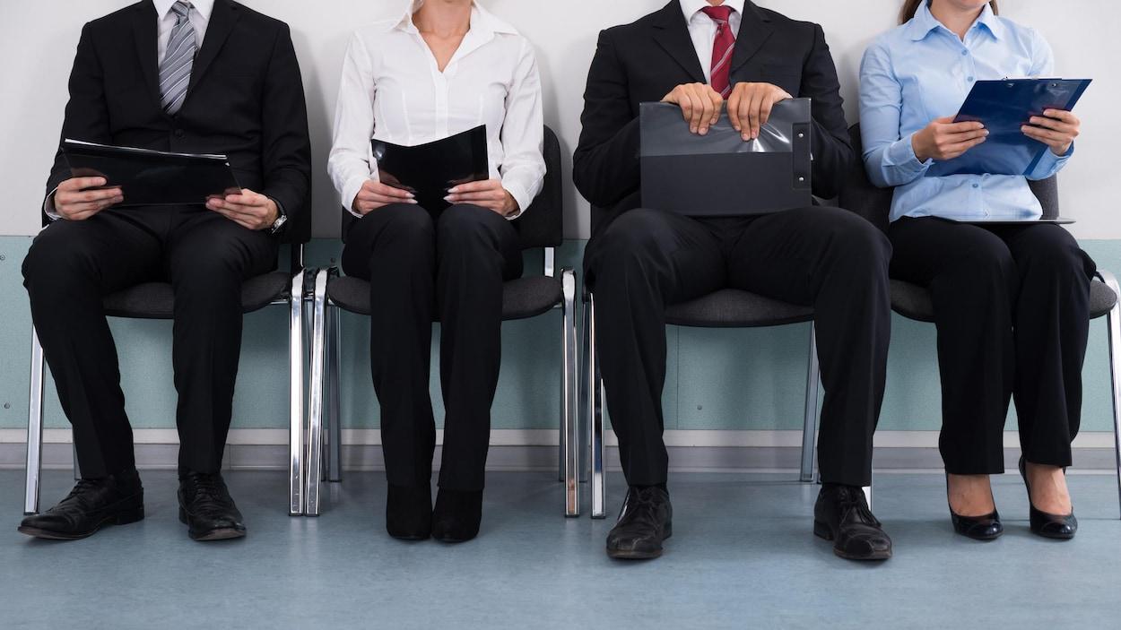 Des candidats attendent pour une entrevue assis en rangée.