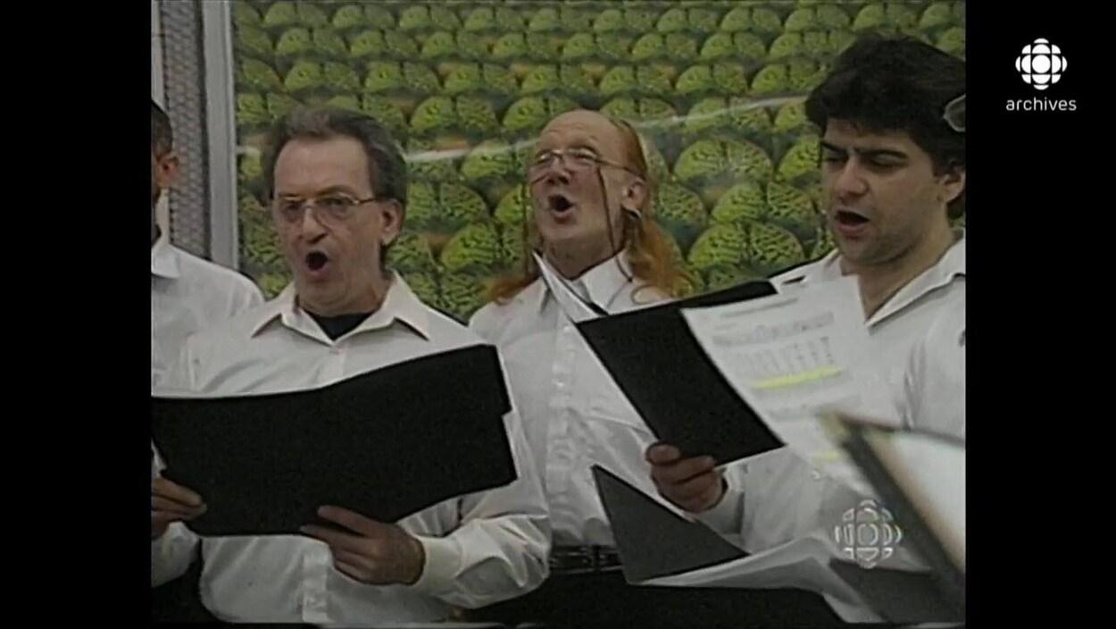 Trois hommes en chemise blanche, partitions à la main, chantent dans un couloir du métro.
