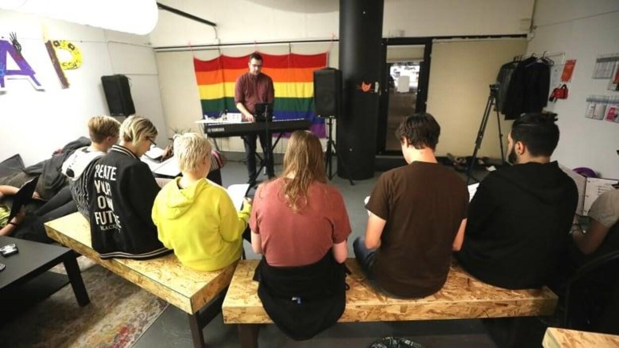 Une personne joue au piano dans une salle. Des jeunes sont assis sur un banc et chantent.