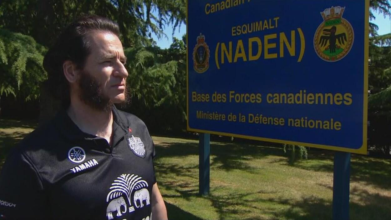 L'homme portant un chandail de sport pose devant le panneau d'entrée de la base militaire.