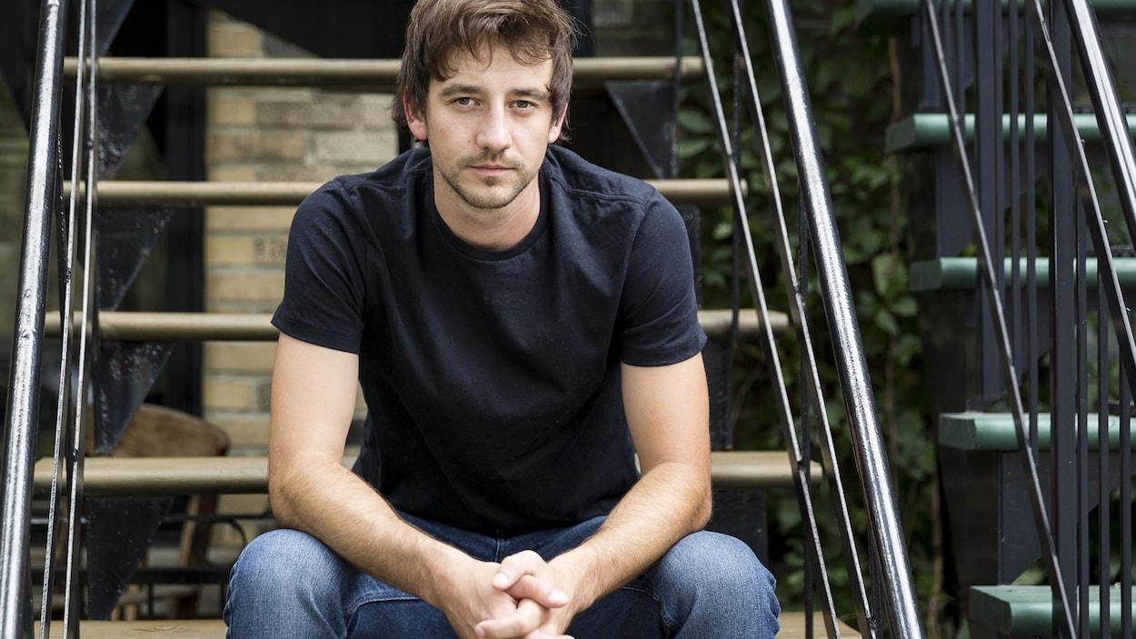 L'écrivain pose assis dans des escaliers