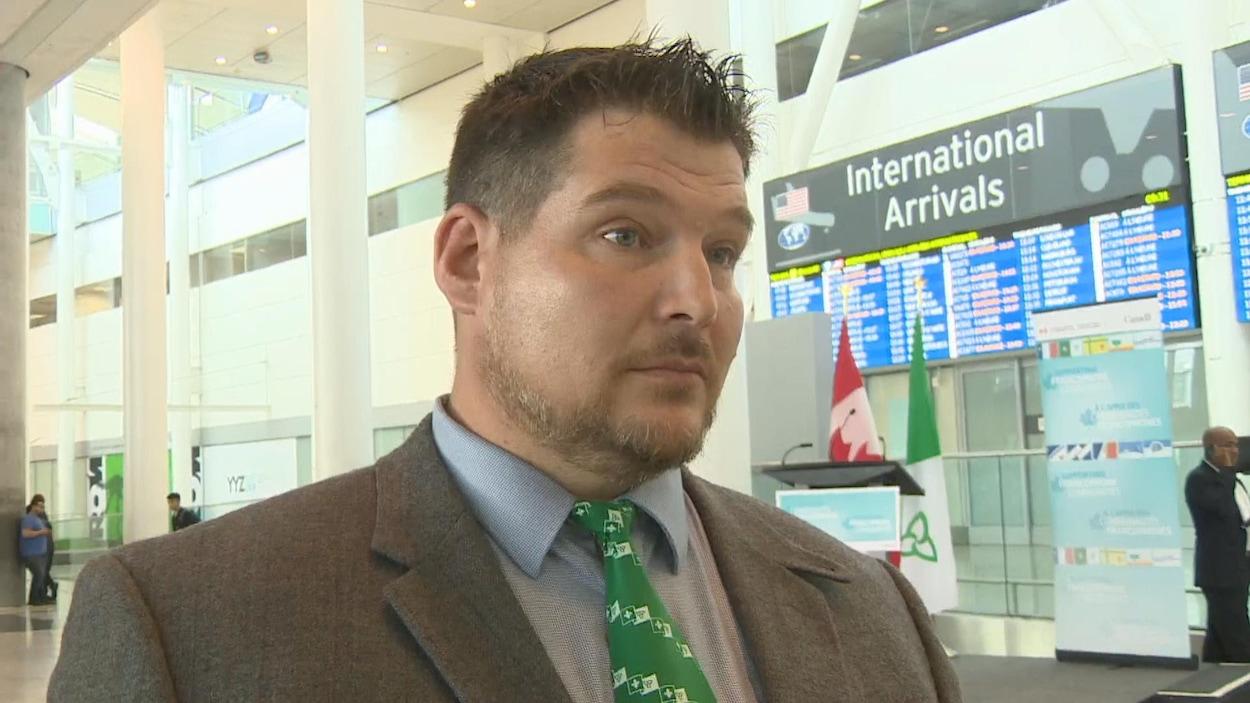 Photo d'un homme en complet portant une cravate avec des drapeaux franco-ontariens devant le tableau d'affichage des arrivées à l'aéroport