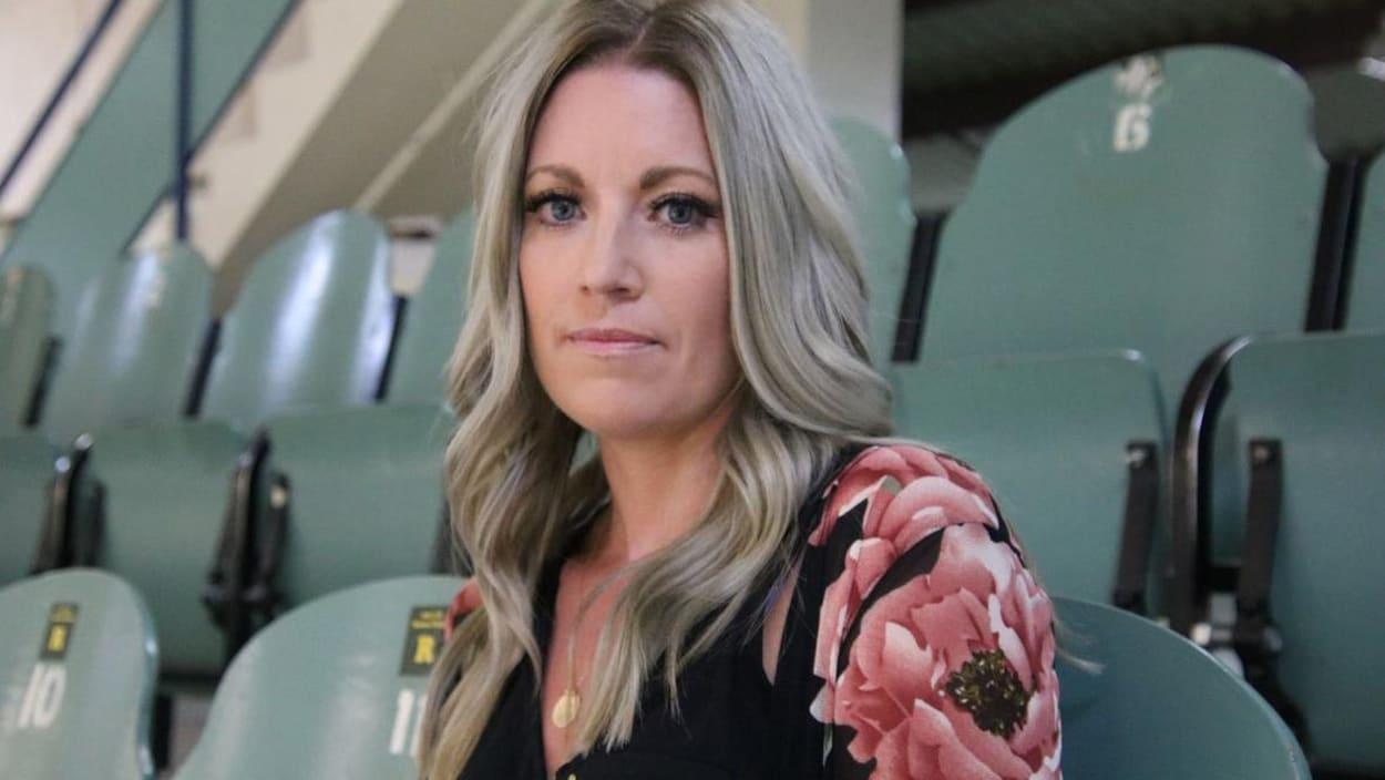 La femme de l'ex-entraîneur des Broncos de Humboldt, Christina Haugan, 42 ans, a les cheveux blonds longs. Elle porte une chemise à fleurs rose et noir. Elle est assise dans un aréna et regarde l'objectif de la caméra.