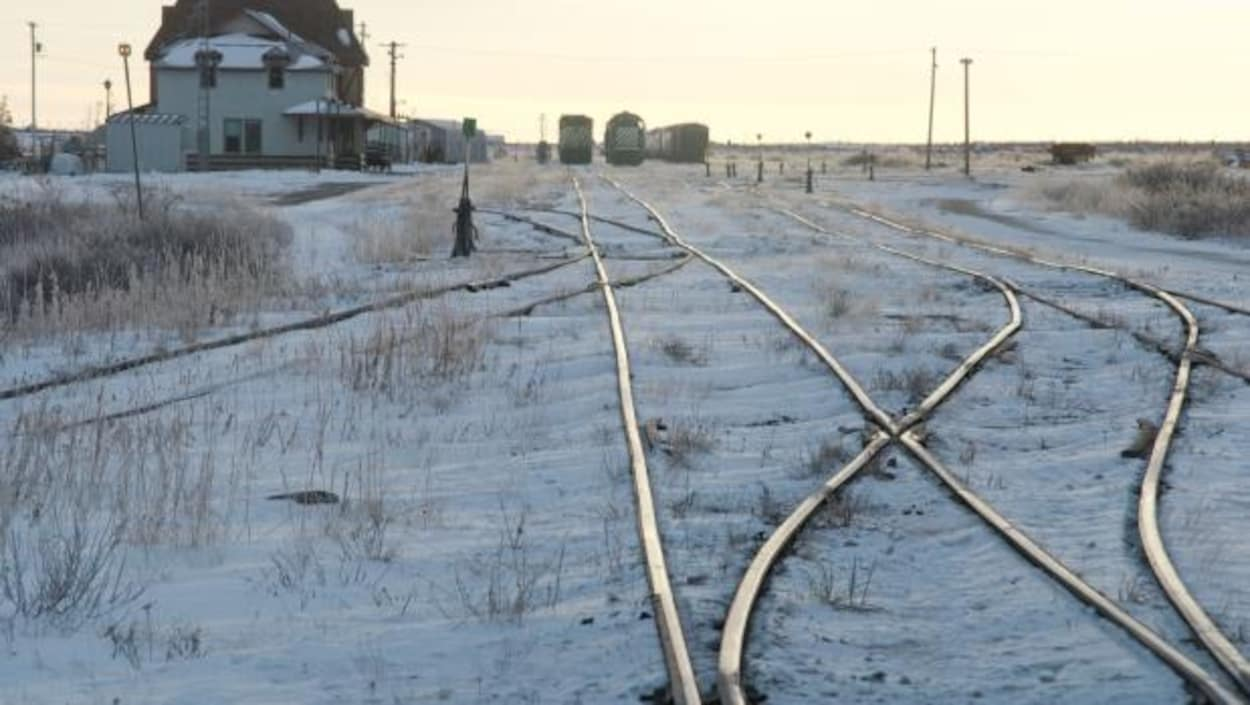 Des chemins de fer entourés de neige et des wagons au loin dans la ville de Churchill au Manitoba.