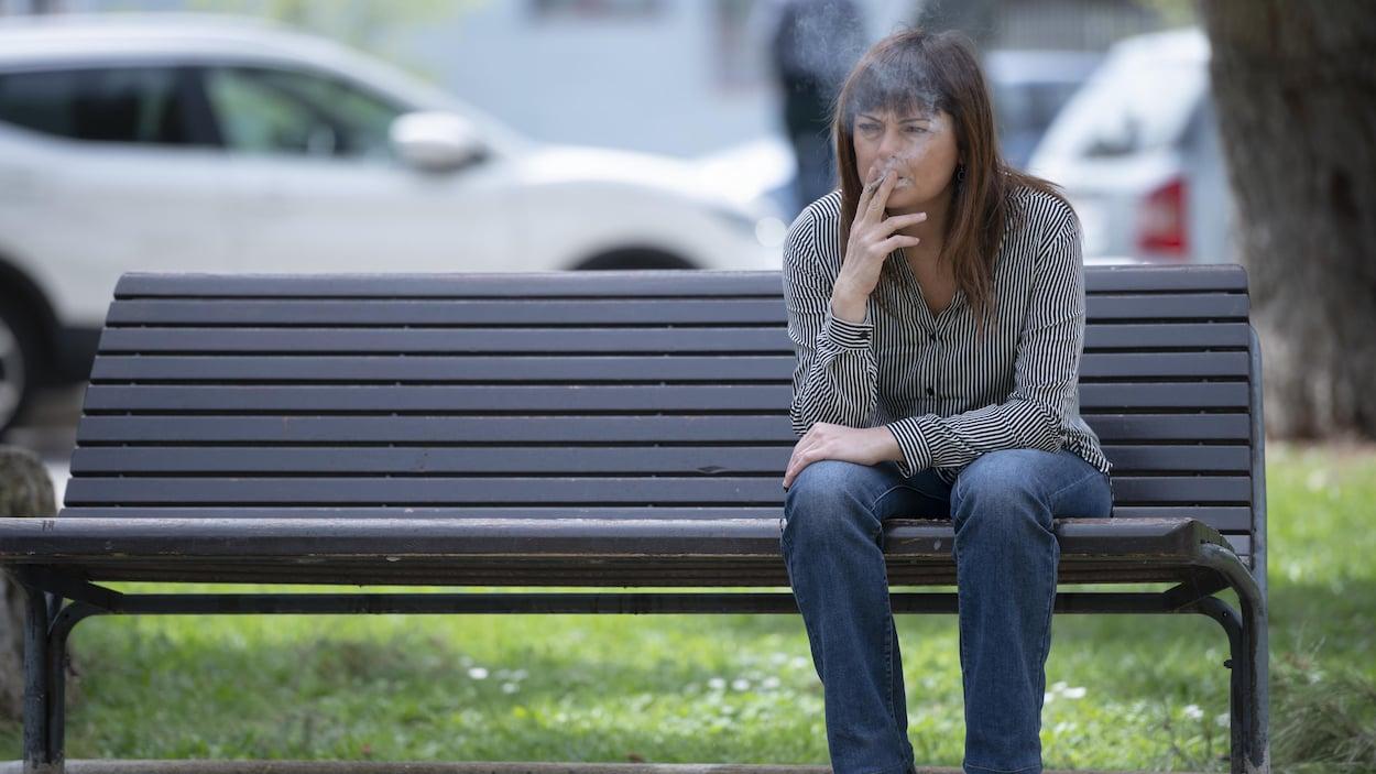 Femme assise sur un banc public, fumant une cigarette.