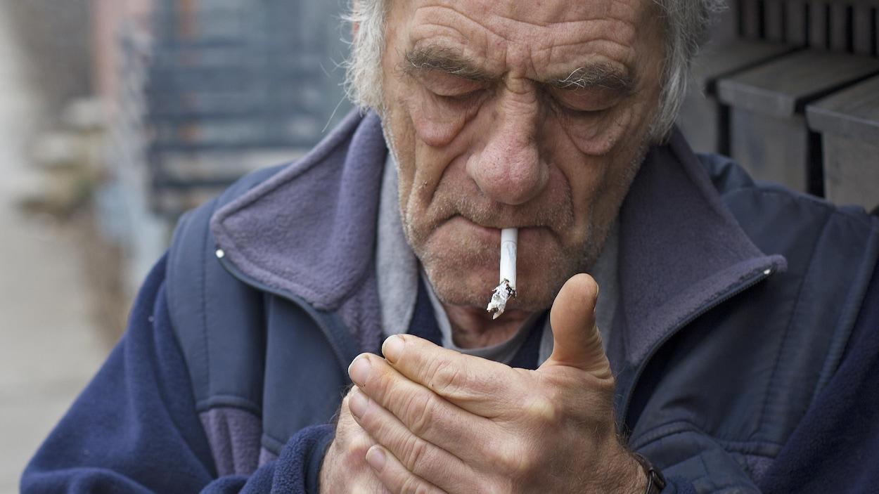 Homme âgé allumant une cigarette à l'extérieur.
