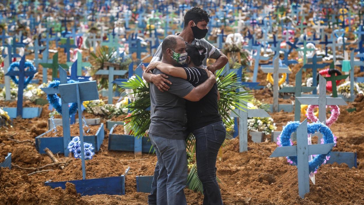 Des gens s'étreignent dans un cimetière.