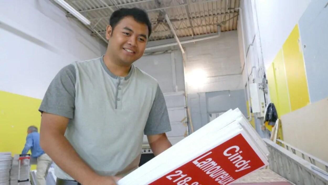 Un bénévole de campagne électorale est dans un entrepot, il tient des pancartes dans ses mains.