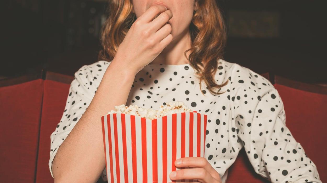 Une femme mange du maïs soufflé au cinéma.