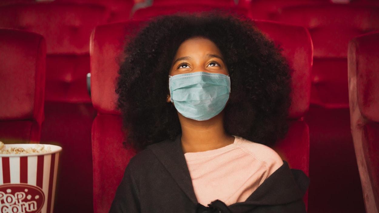 Une jeune fille portant un masque de protection est assise dans une salle de cinéma, avec un popcorn.