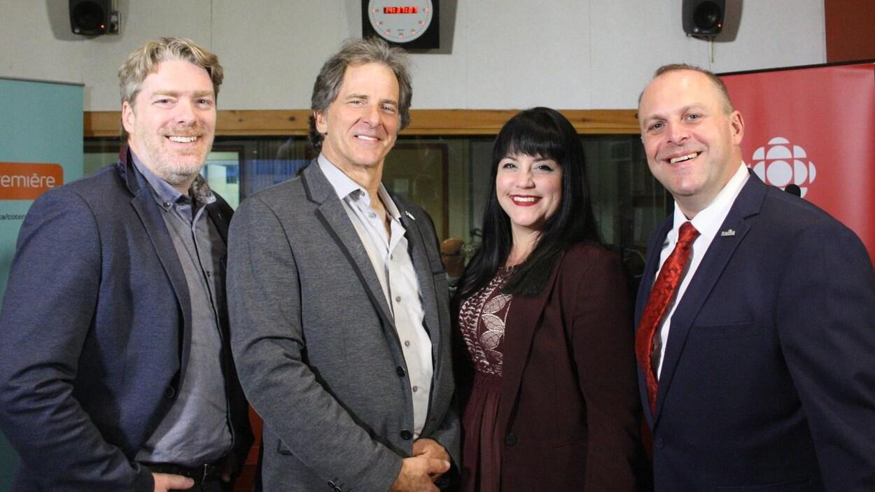 Les quatre candidats sourient à la caméra, dans le studio radio de Radio-Canada.