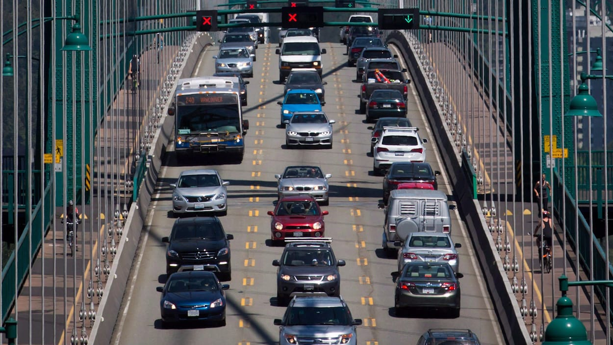Des voitures, un autobus et des cyclistes traversent un pont.