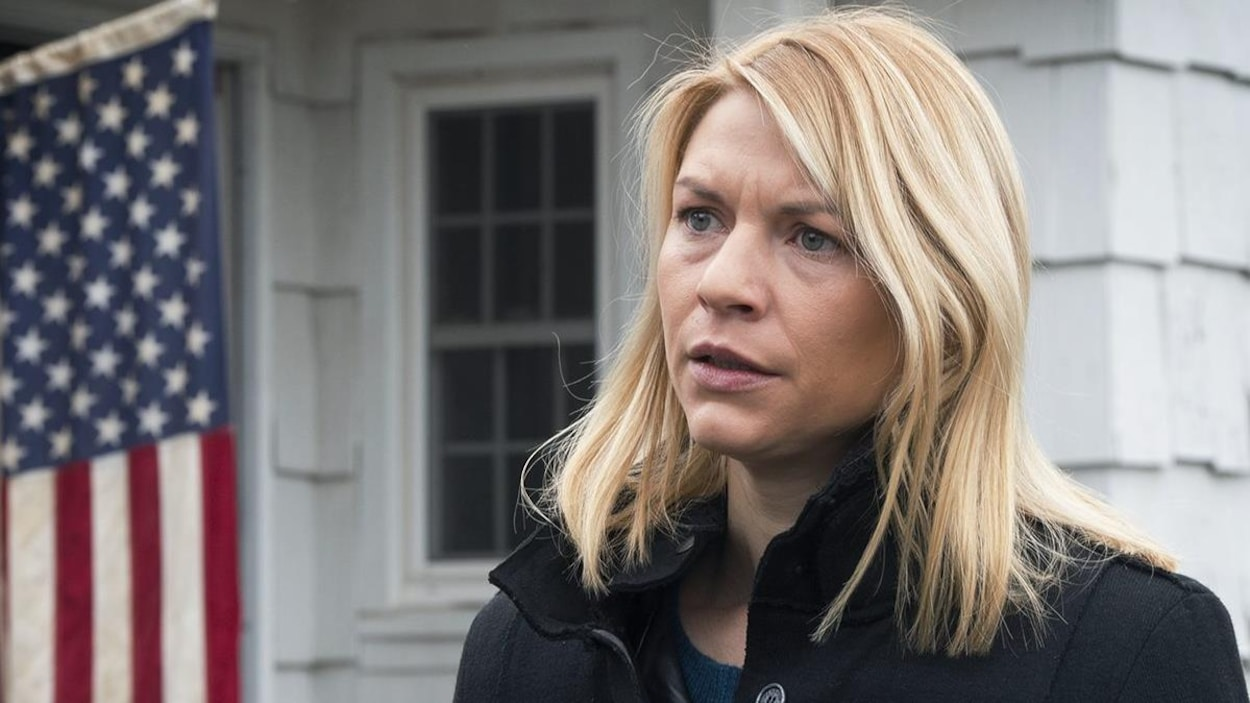 Claire Danes regarde quelqu'un devant une maison où l'on peut voir le drapeau américain, dans une scène de la série <i>Homeland</i>.