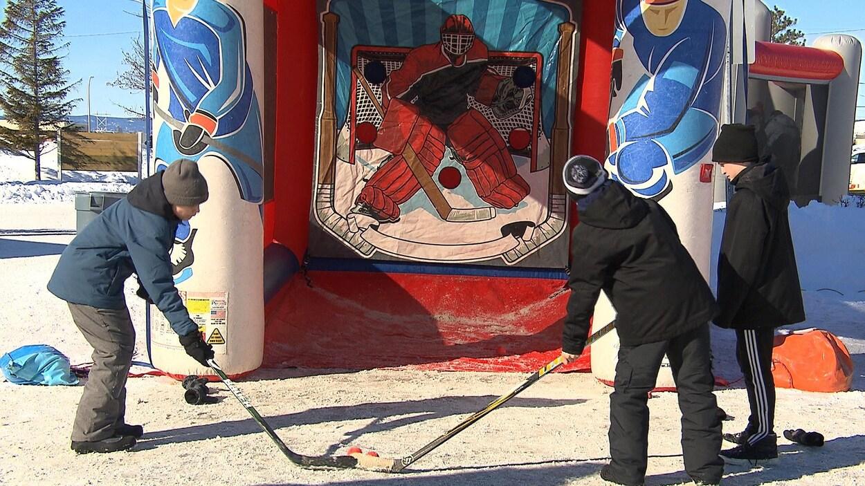 Deux élèves s'exercent à lancer avec plus de précision sur une cible représentant un gardien de but de hockey.