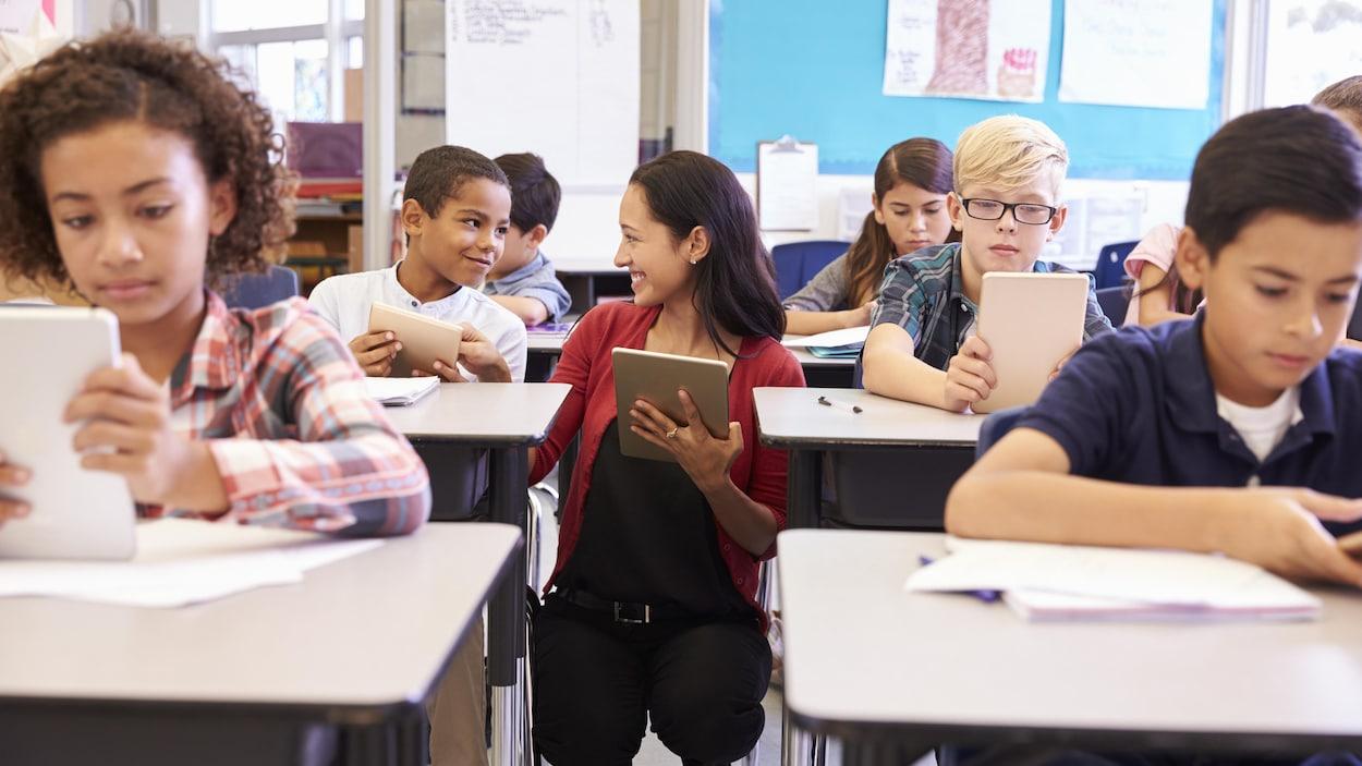 Des élèves d'âge primaire dans une classe, tous équipés d'une tablette électronique.