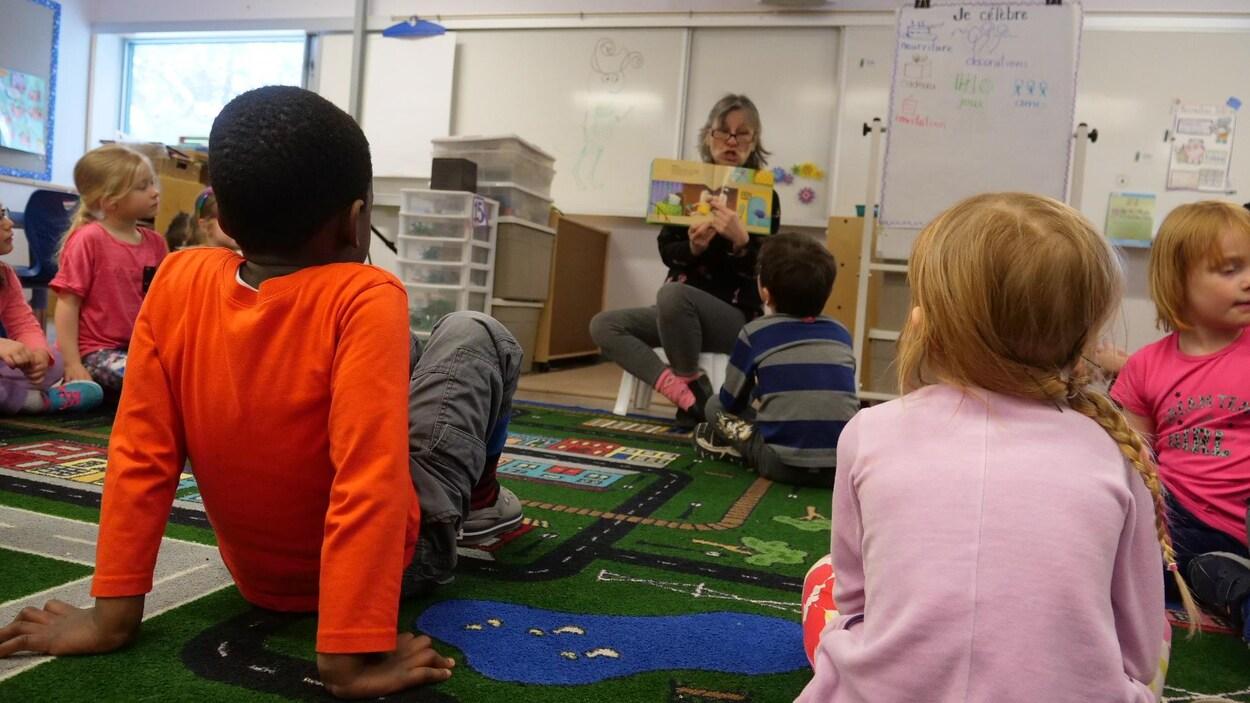 Des enfants assis par terre dans une classe. Devant eux, l'enseignante leur raconte une histoire en leur montrant les images d'un livre.