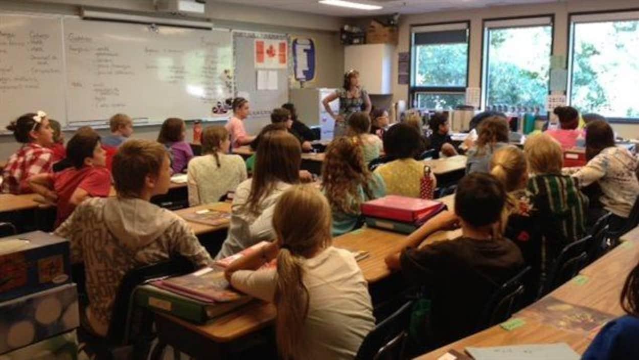 Des élèves du pavillon élémentaire de l'École canadienne-française de Saskatoon écoutent leur enseignante en classe.