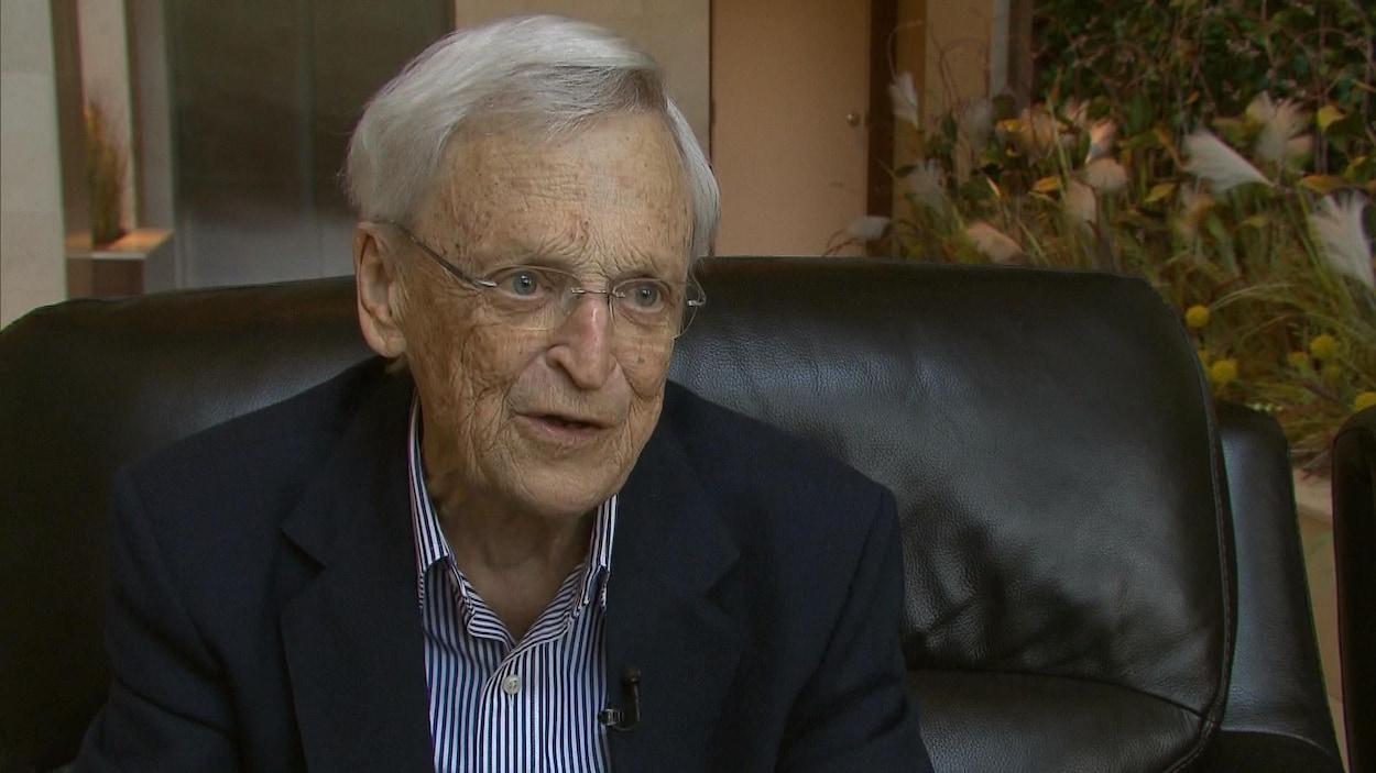 Claude Béland assis dans un fauteuil répond aux questions d'une journaliste.