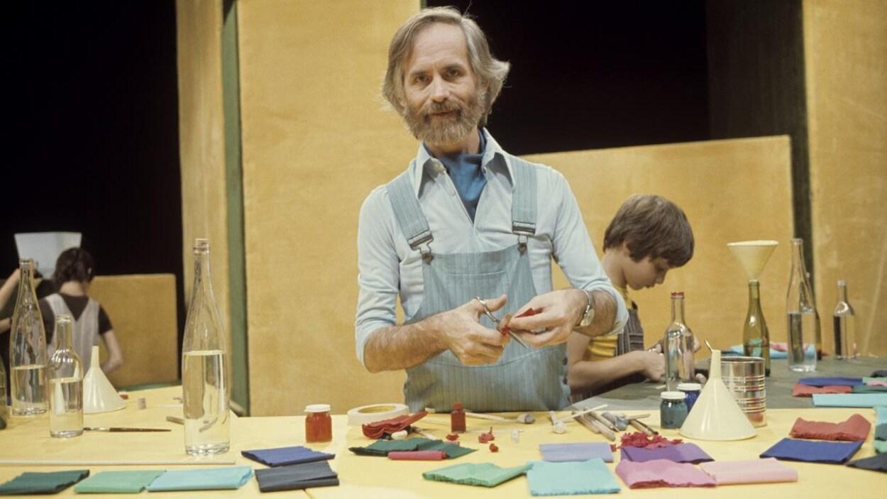 Dans un studio de télévision, l'animateur Claude Lafortune est debout à la table de bricolage.
