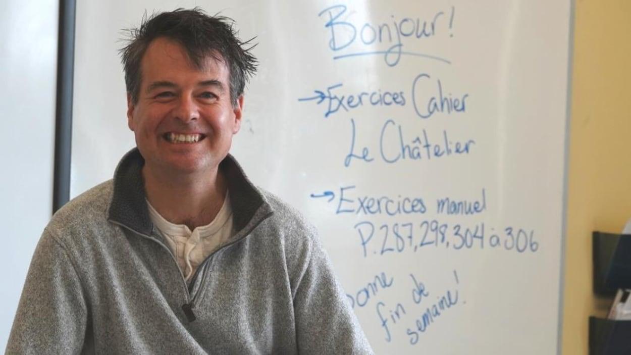 Claude Vallée dans sa classe assis sur son bureau.