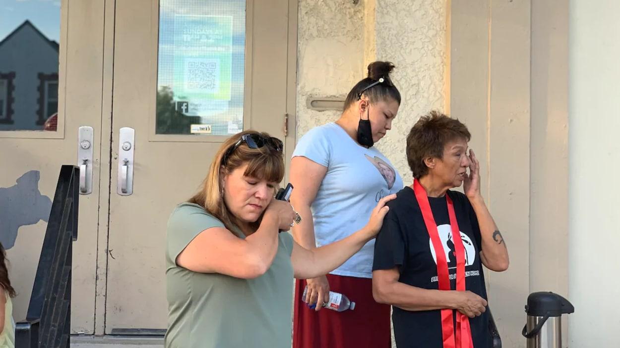 Trois femmes émues essuient des larmes.