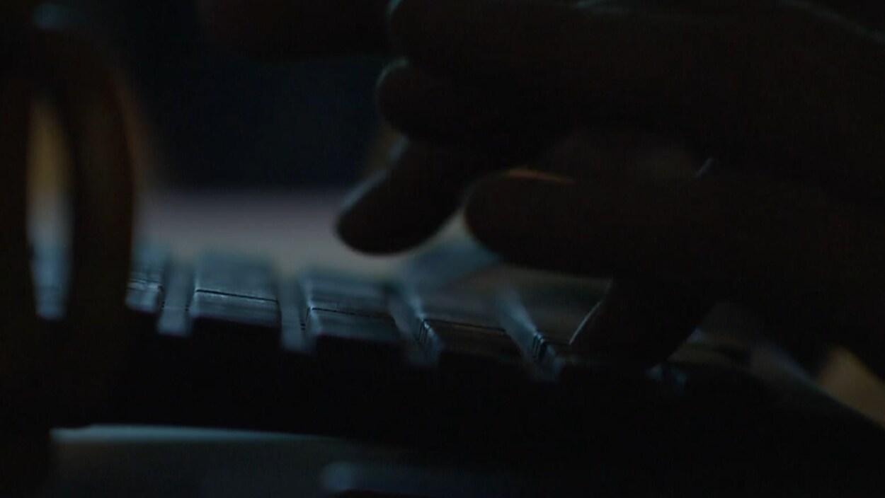 Des doigts tapent sur un clavier dans une pièce sombre.