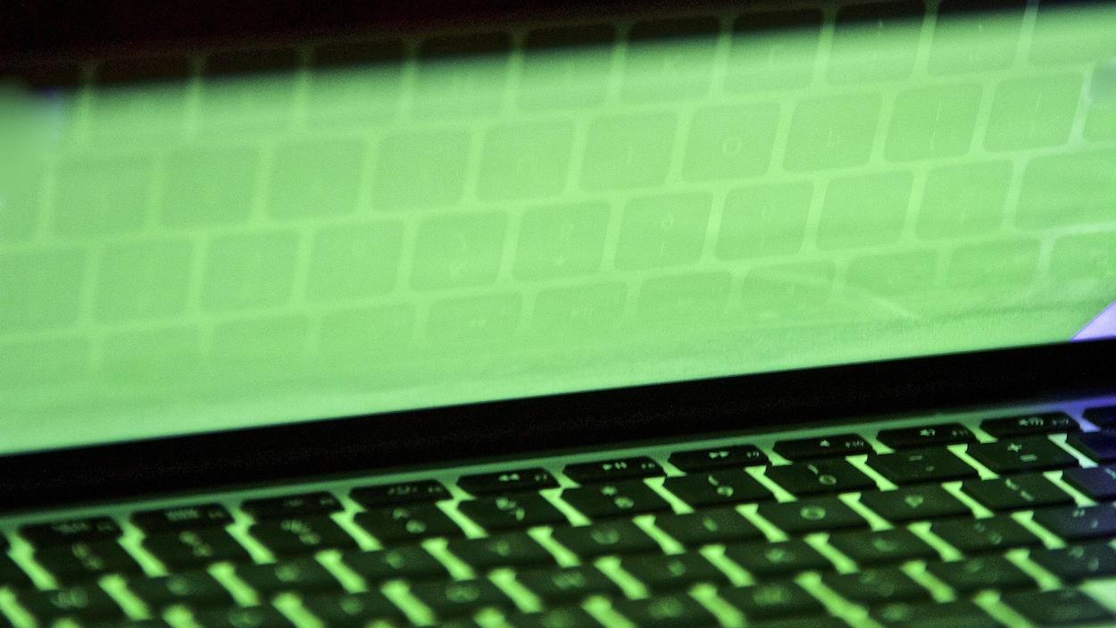 Un clavier d'ordinateur portatif se reflète sur un écran.