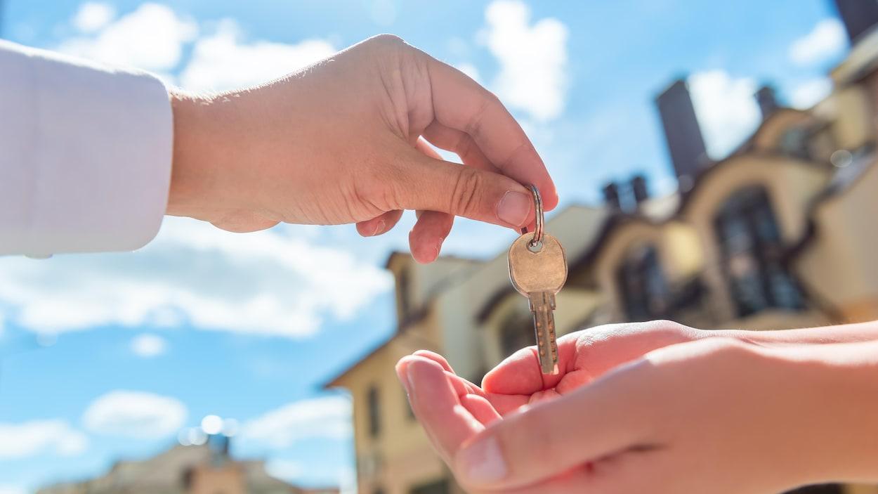 Deux mains s'échangent une clef d'un logement.