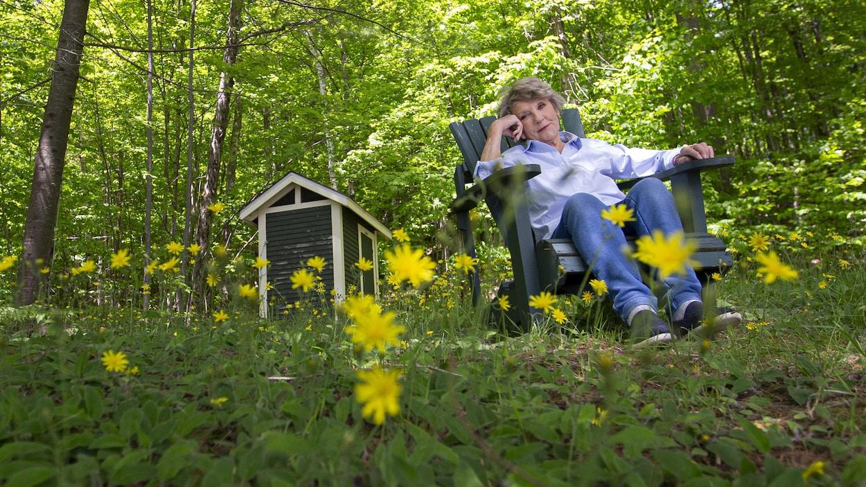 Clémence DesRochers, assise à la campagne.