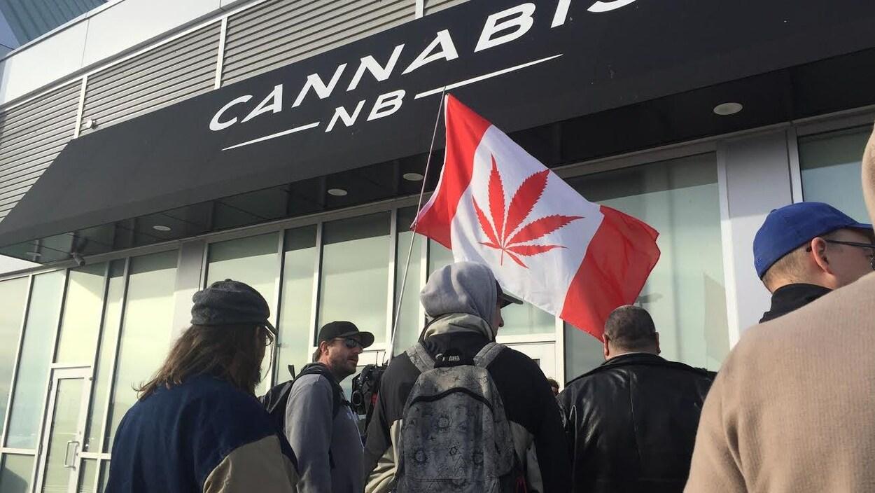 Des clients devant une succursale de Cannabis NB, avec un drapeau canadien où la feuille d'un plant de marijuana remplace la feuille d'érable.