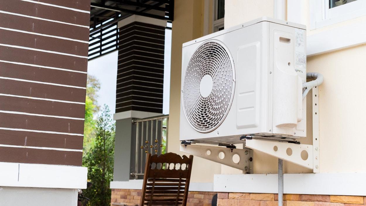 Un climatiseur fixé au mur d'une maison.