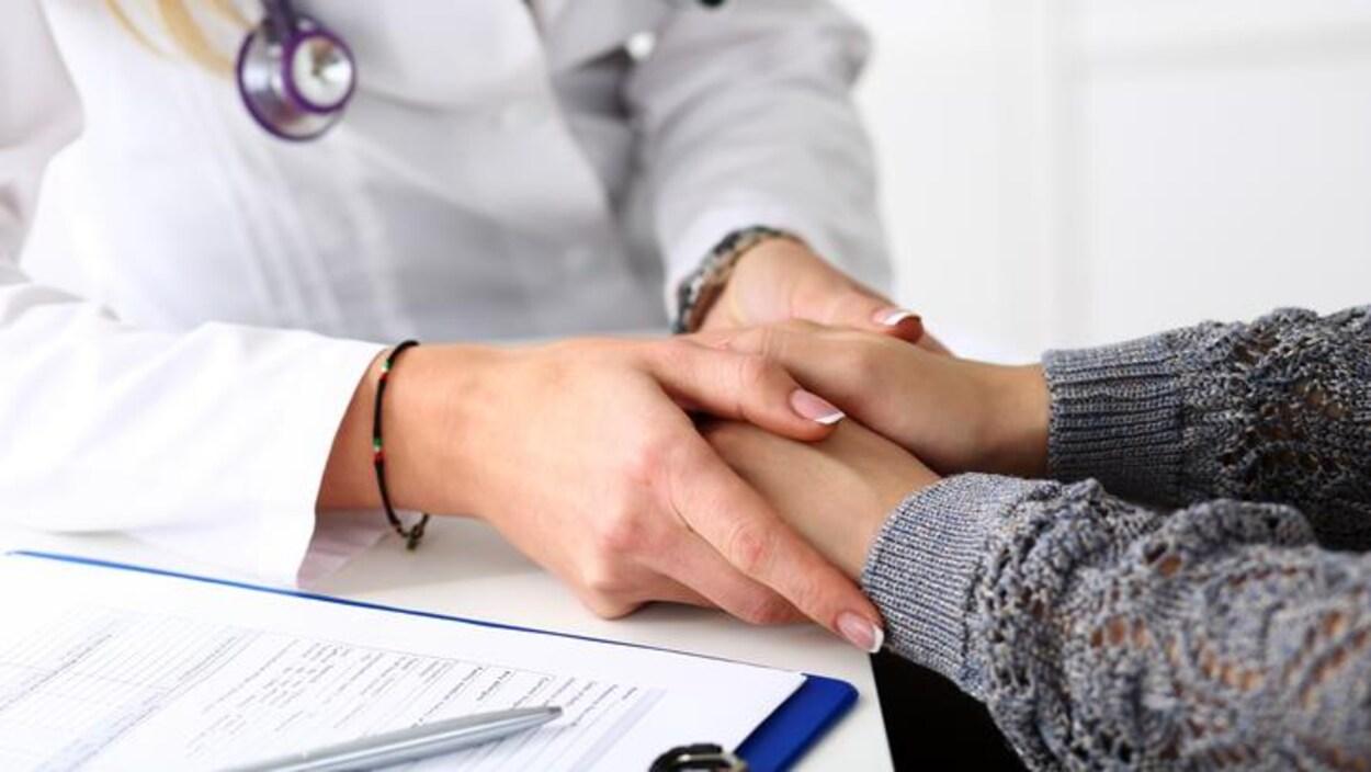 Un médecin prend les mains d'une patiente.
