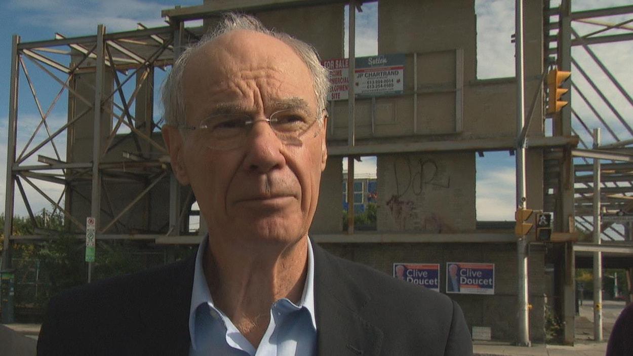 Clive Doucet en point de presse devant un bâtiment désaffecté.
