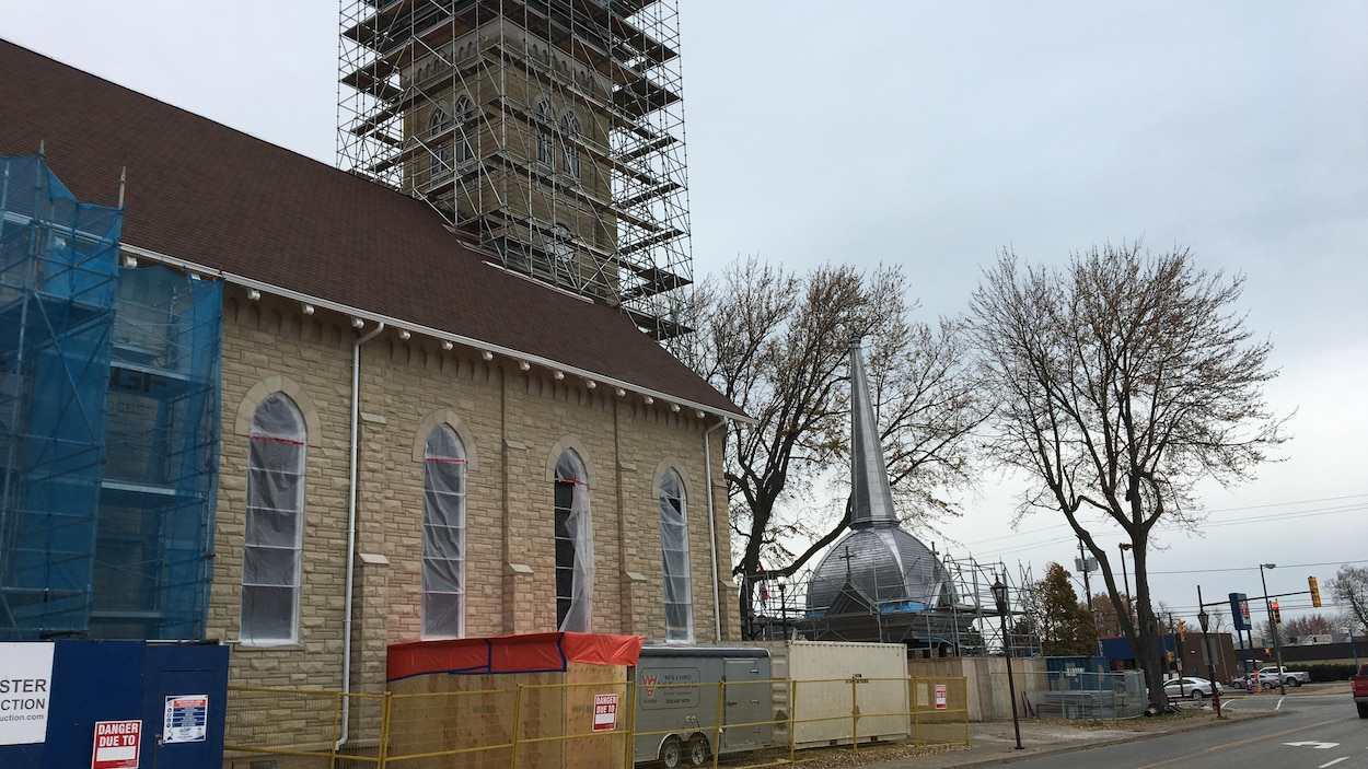 On peut voir une église en réaparation. Des échafauds sont placés autour de la tour et le clocher est sur le sol, devant le bâtiment.