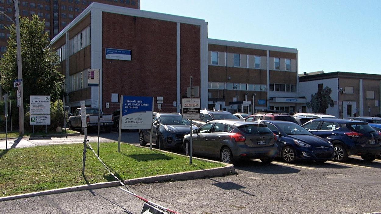 Des véhicules sont stationnés devant un édifice.