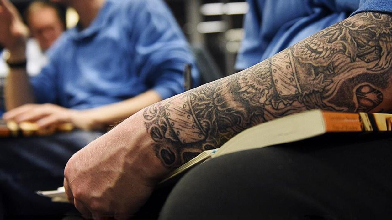 Un homme tatoué habillé d'un chandail bleu s'appuie sur un livre.