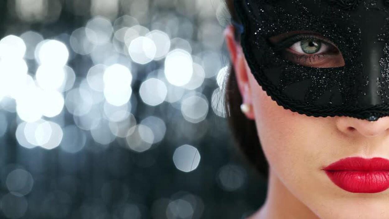 Image tirée du site web du club privé d'effeuillage Regina 151. Gros plan sur le visage d'une femme portant un loup et du rouge à lèvres rouge. L'arrière-plan est flou et composé de billes lumineuses.