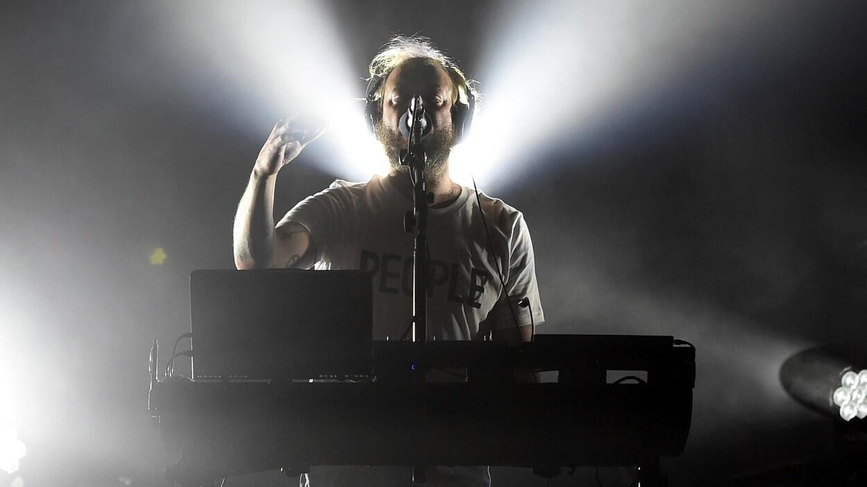 Un musicien portant des écouteurs se tient derrière un ordinateur portable et une table de mixage, sur une scène de spectacle.