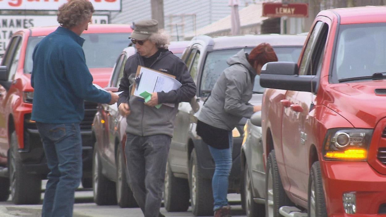 Trois personnes accostent des gens dans leur automobile pour leur faire signer une pétition.