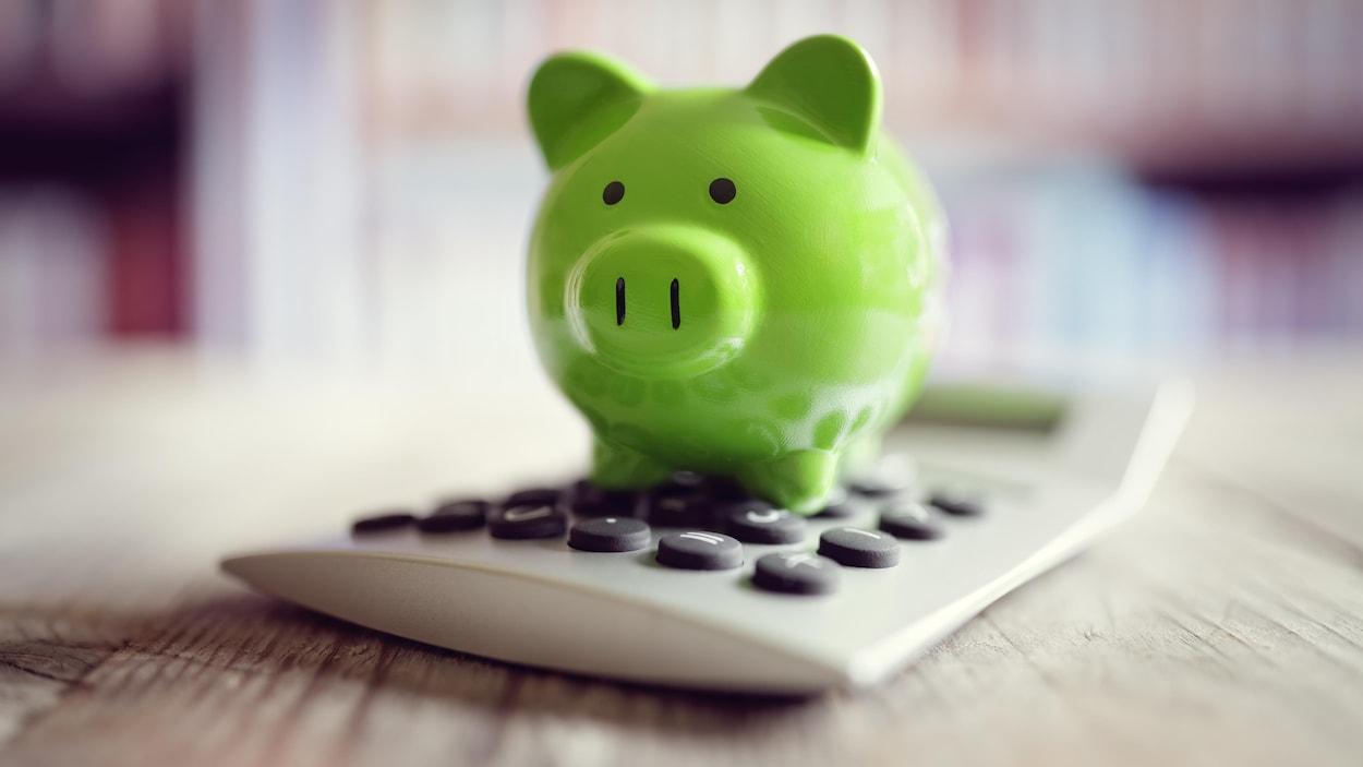 Un cochon vert en porcelaine sur une calculatrice.